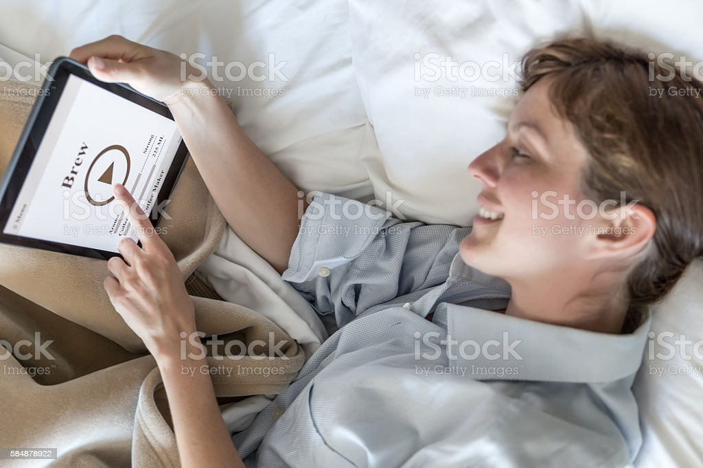 Woman in Bed Using Coffee maker Application on Digital Tablet stock photo