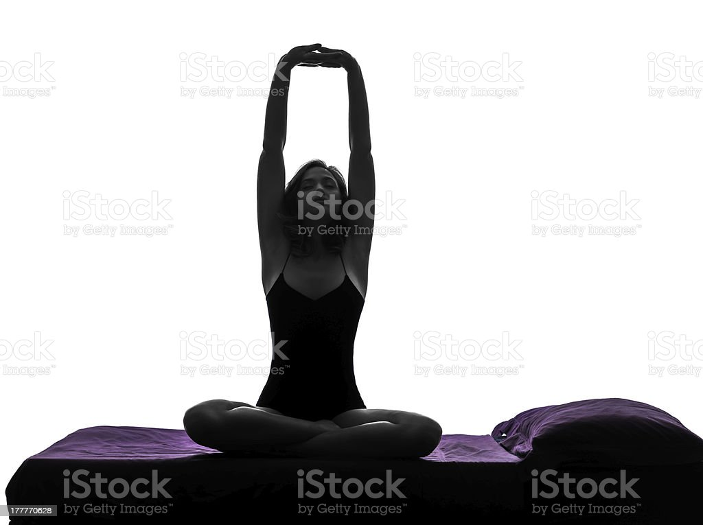 woman in bed waking up stretching arms silhouette royalty-free stock photo
