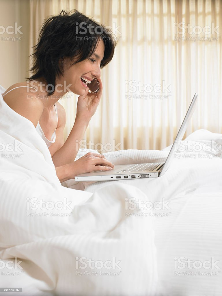 Woman in bed with computer royalty-free stock photo