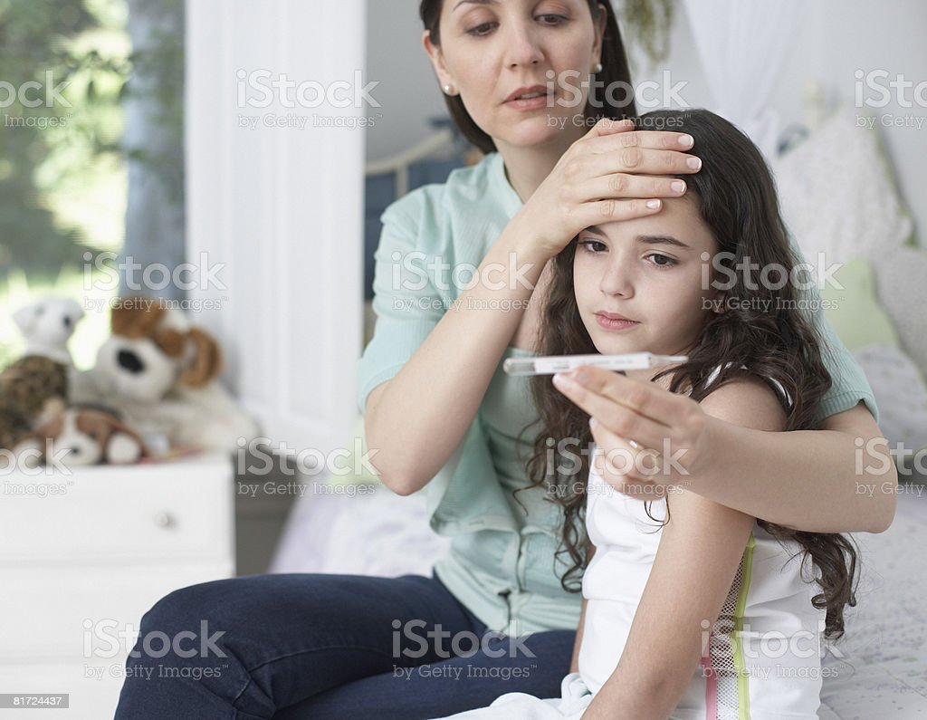 Woman in bedroom taking young girls temperature stock photo