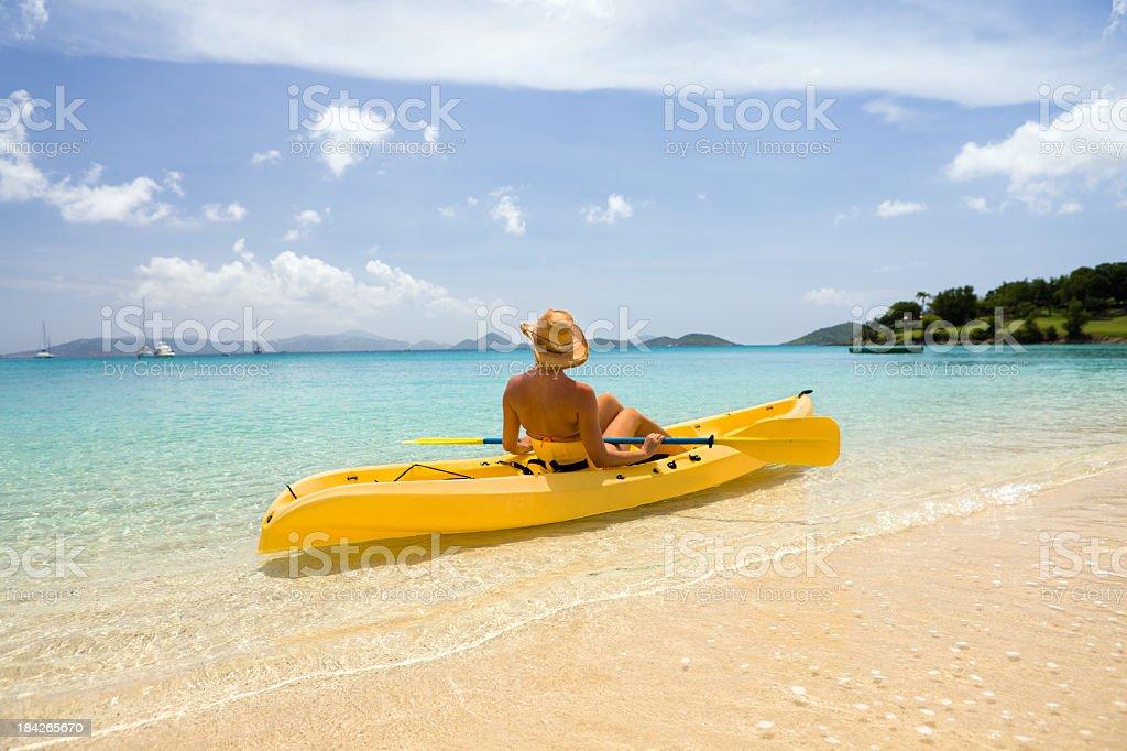 woman in bikini getting ready to kayak the Caribbean bay royalty-free stock photo