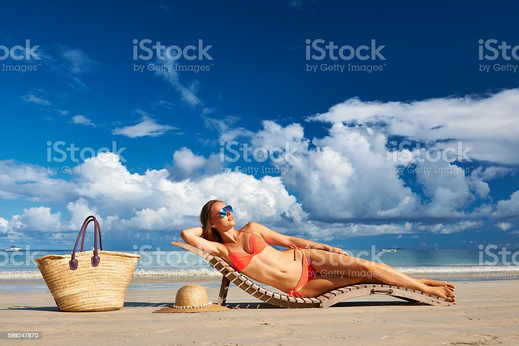 Woman in bikini lying on beach at Seychelles stock photo