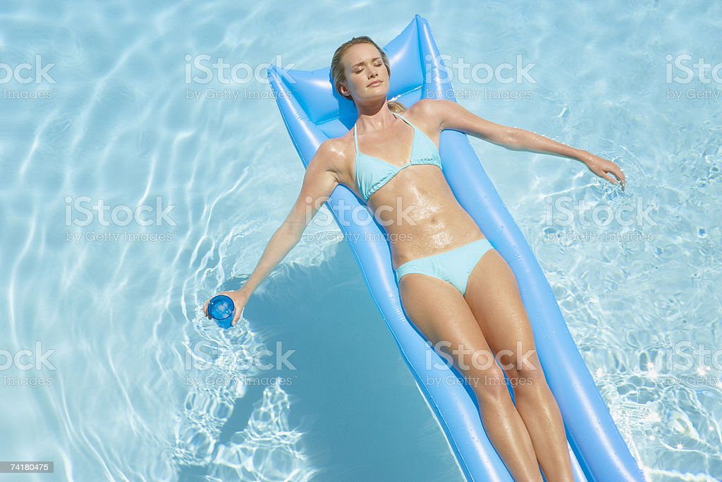 Woman in bikini on flotation device in pool with beverage royalty-free stock photo