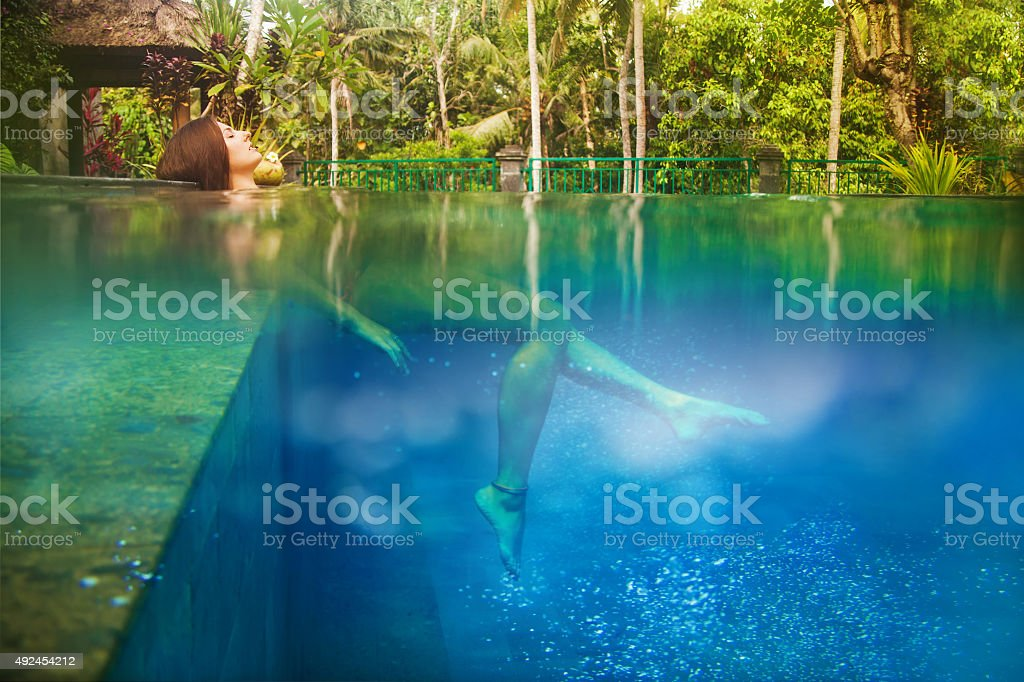 Woman in bikini relaxing in tropical swimming pool stock photo
