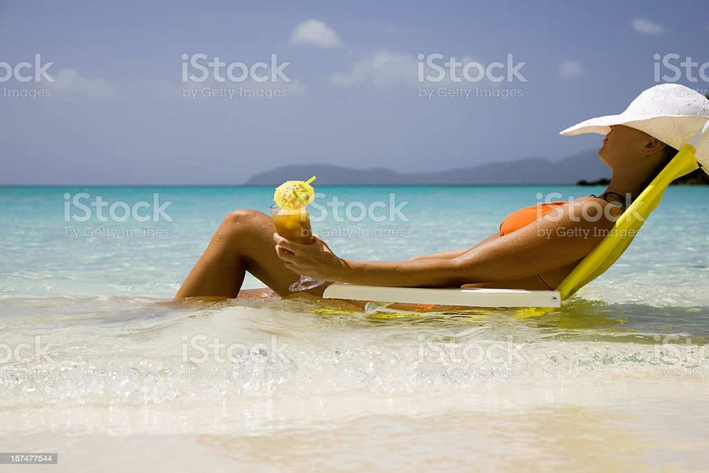 woman in bikini relaxing with a cocktail royalty-free stock photo