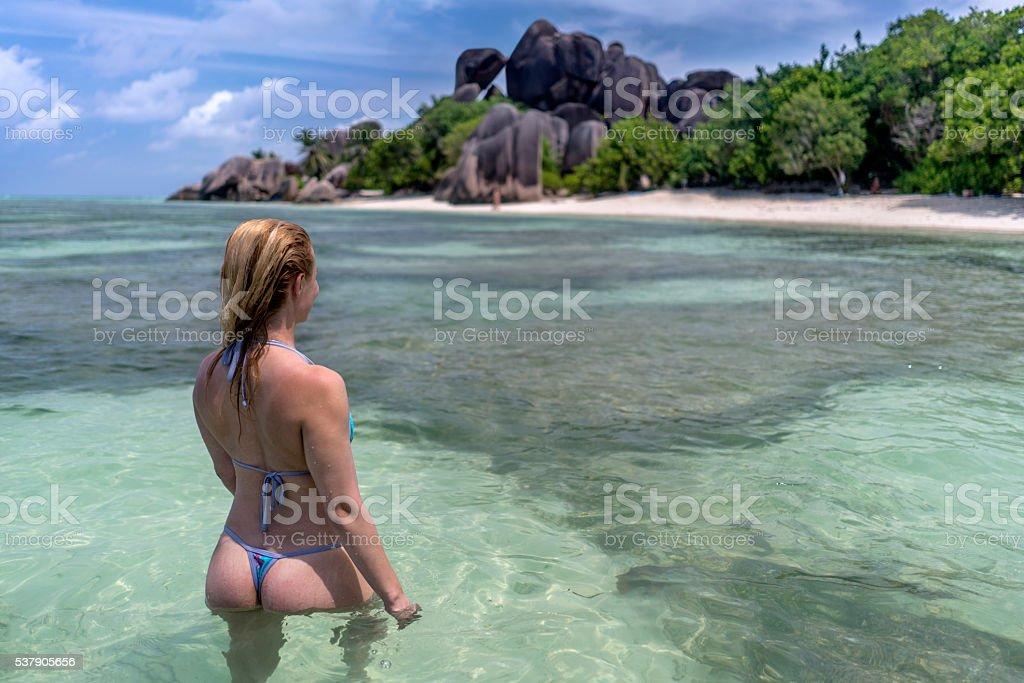 Woman in bikini walking through sea on La Digue island. stock photo
