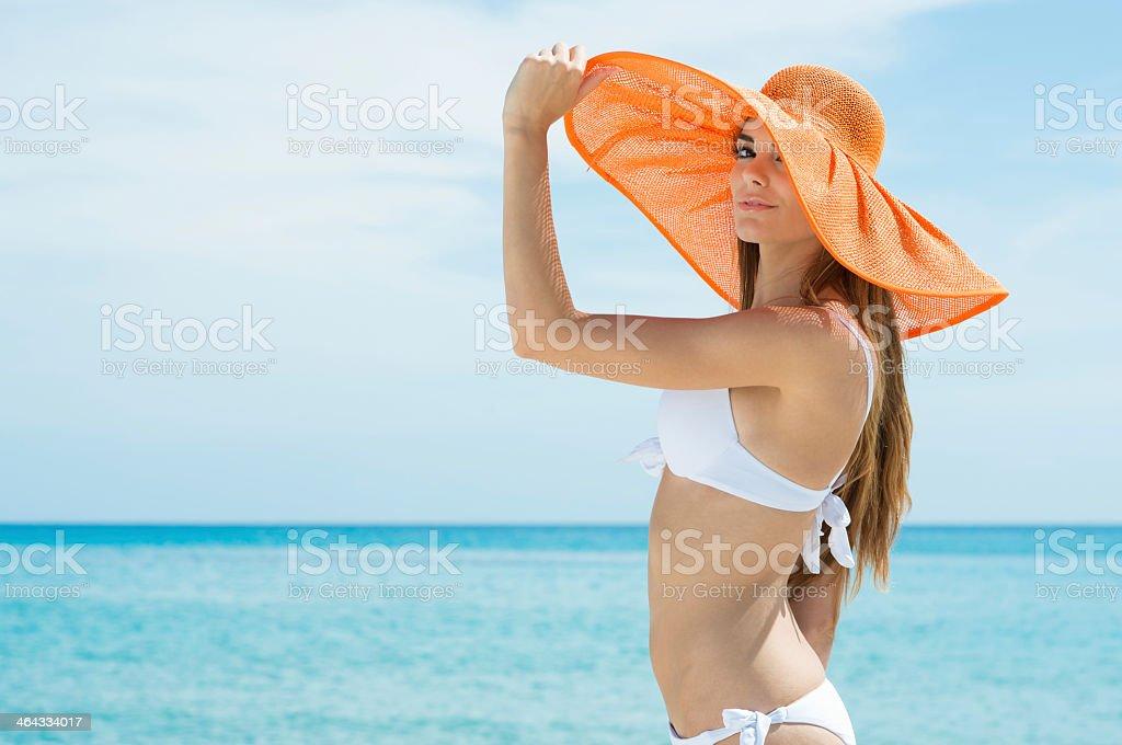 Woman in bikini wearing large orange straw hat by the sea stock photo
