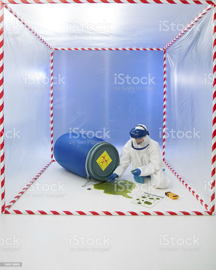 Woman in  biohazard suit testing a spill stock photo