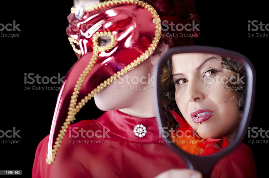 Woman in bird bill mask holding mirror for other. stock photo
