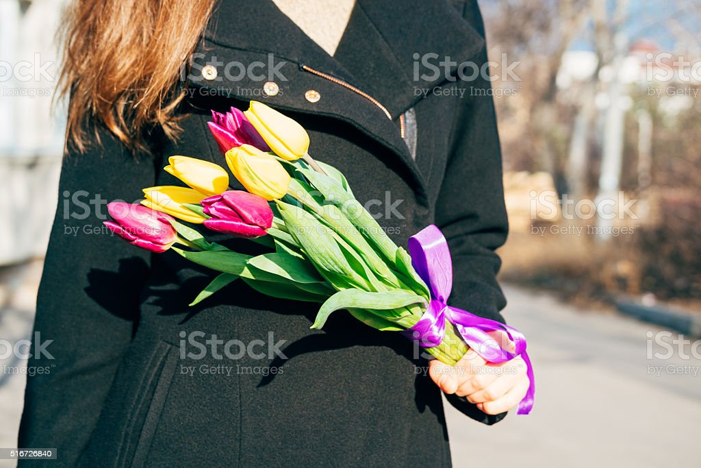 Woman in black coat holding a bright bouquet of flowers stock photo