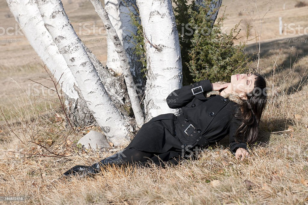 Woman in Black Coat Lying on Grass by Birch royalty-free stock photo