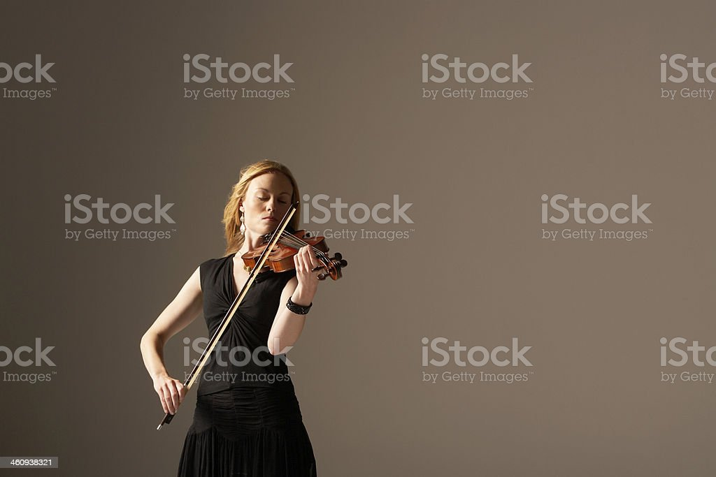 Woman in black dress playing the violin stock photo