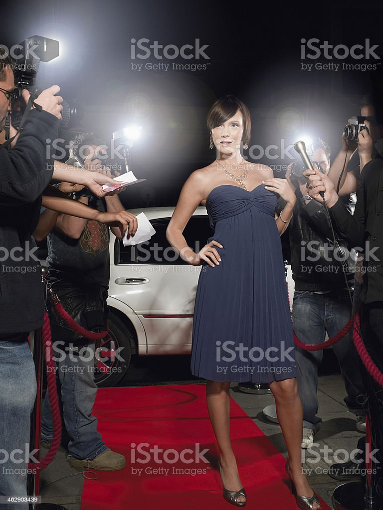 Woman in black dress poses on a red carpet stock photo