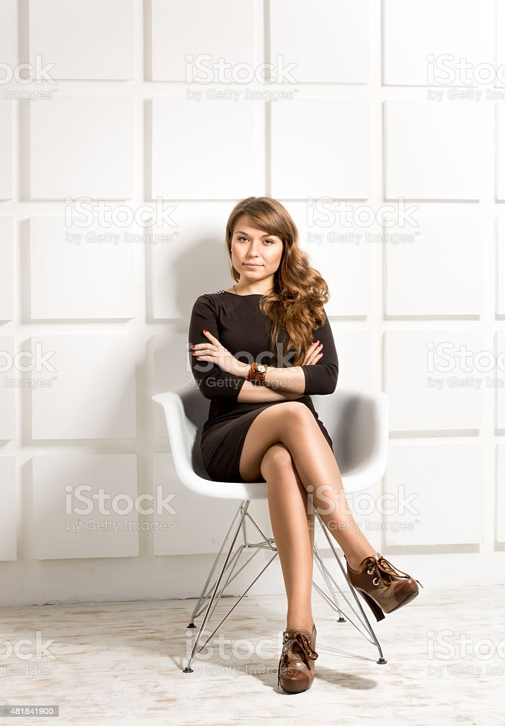 woman in black dress posing in white chair at studio stock photo