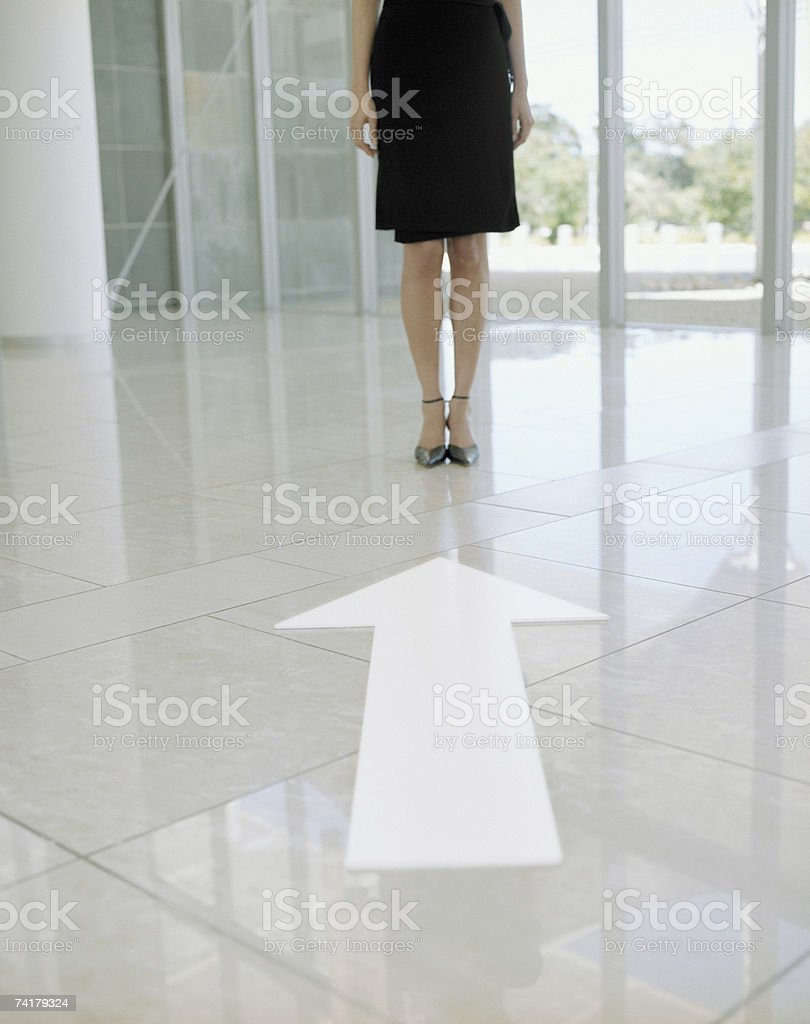 Woman in black dress with large windows with blank arrow pointing at feet waist down royalty-free stock photo