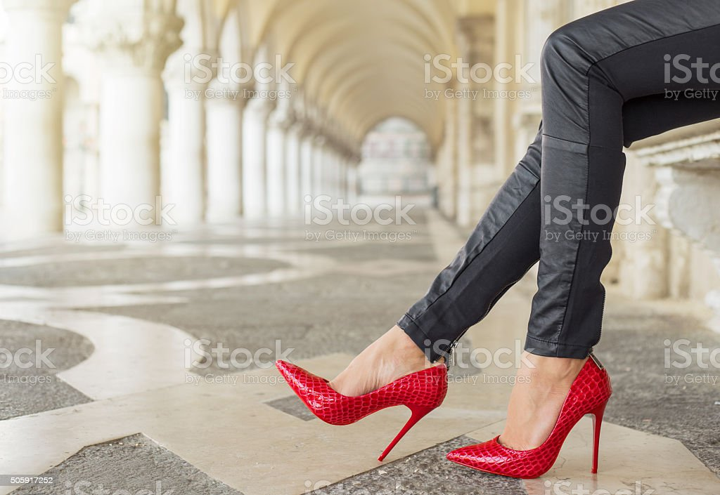 Woman in black leather pants and red high heel shoes stock photo