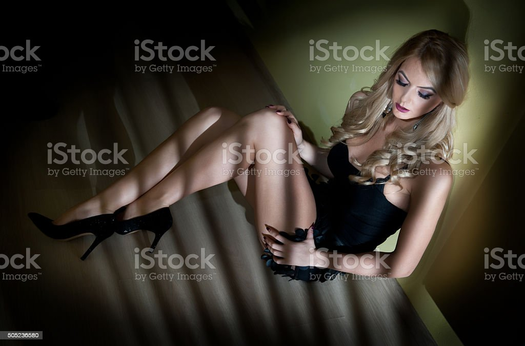 woman in black lingerie sitting on the floor stock photo