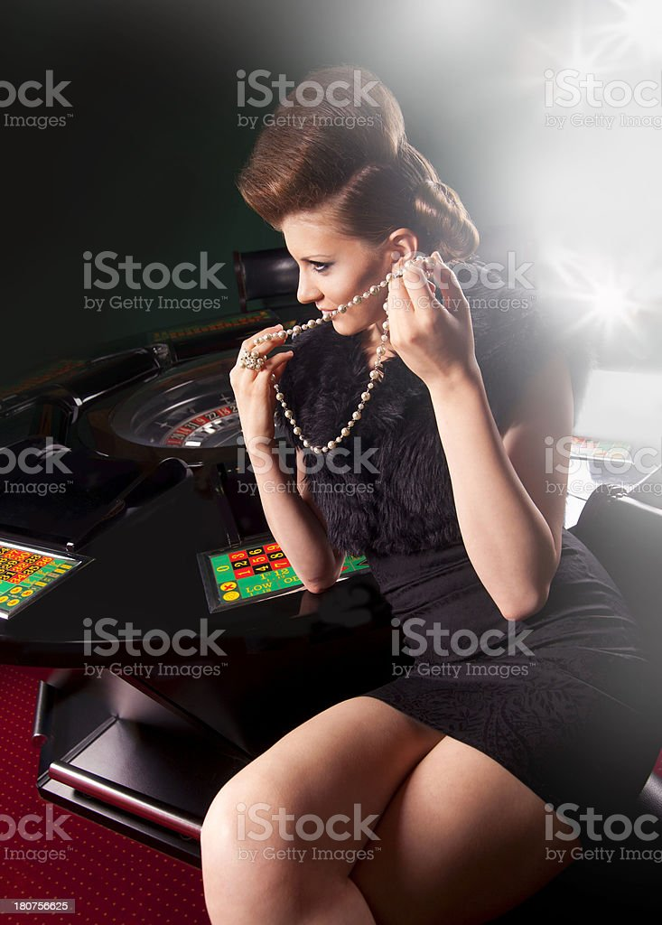 woman in black sitting at roulette table royalty-free stock photo