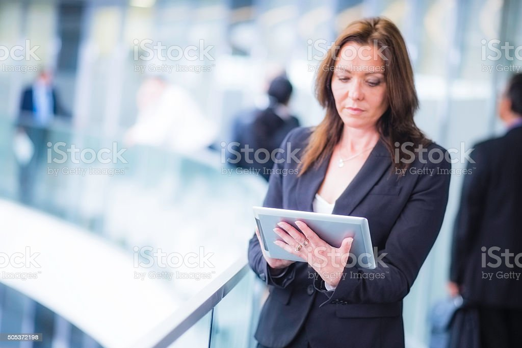 Woman in black using digital tablet in office hallway stock photo