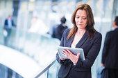 Woman in black using digital tablet in office hallway