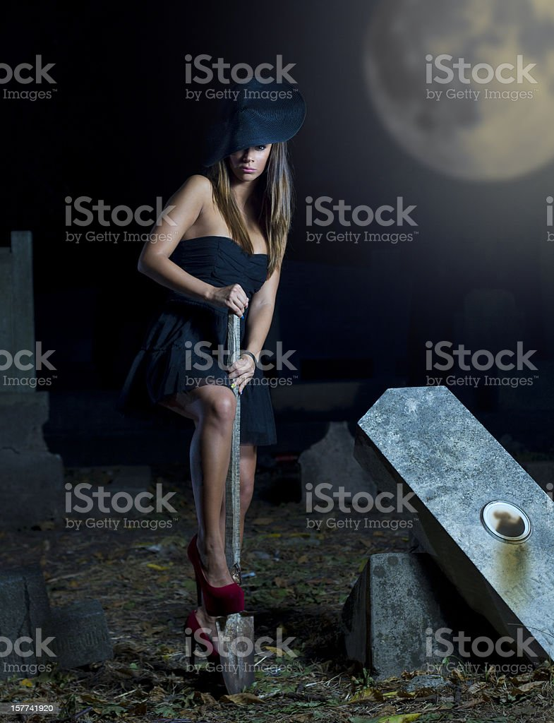 Woman in black with showel on graveyard stock photo