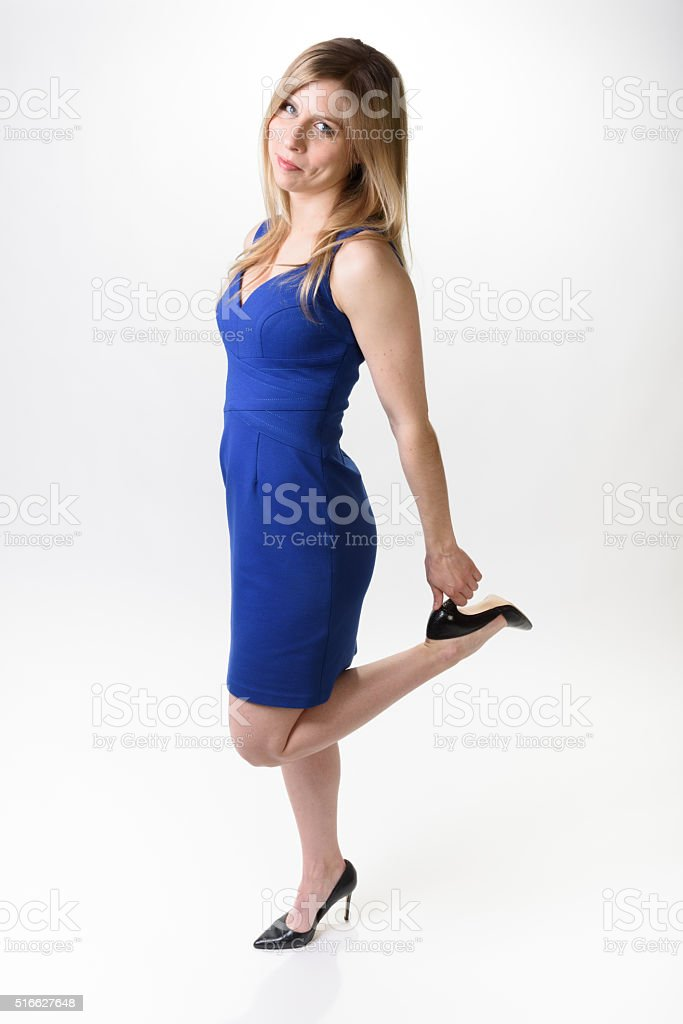 Woman in blue dress holding heels stock photo