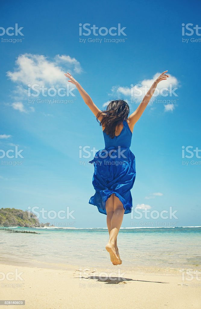 Woman in blue dress on the beach stock photo