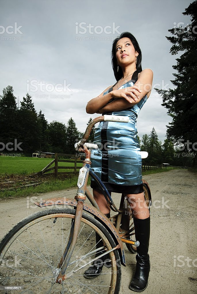 Woman in Blue Dress Sitting on Vintage Bicycle royalty-free stock photo