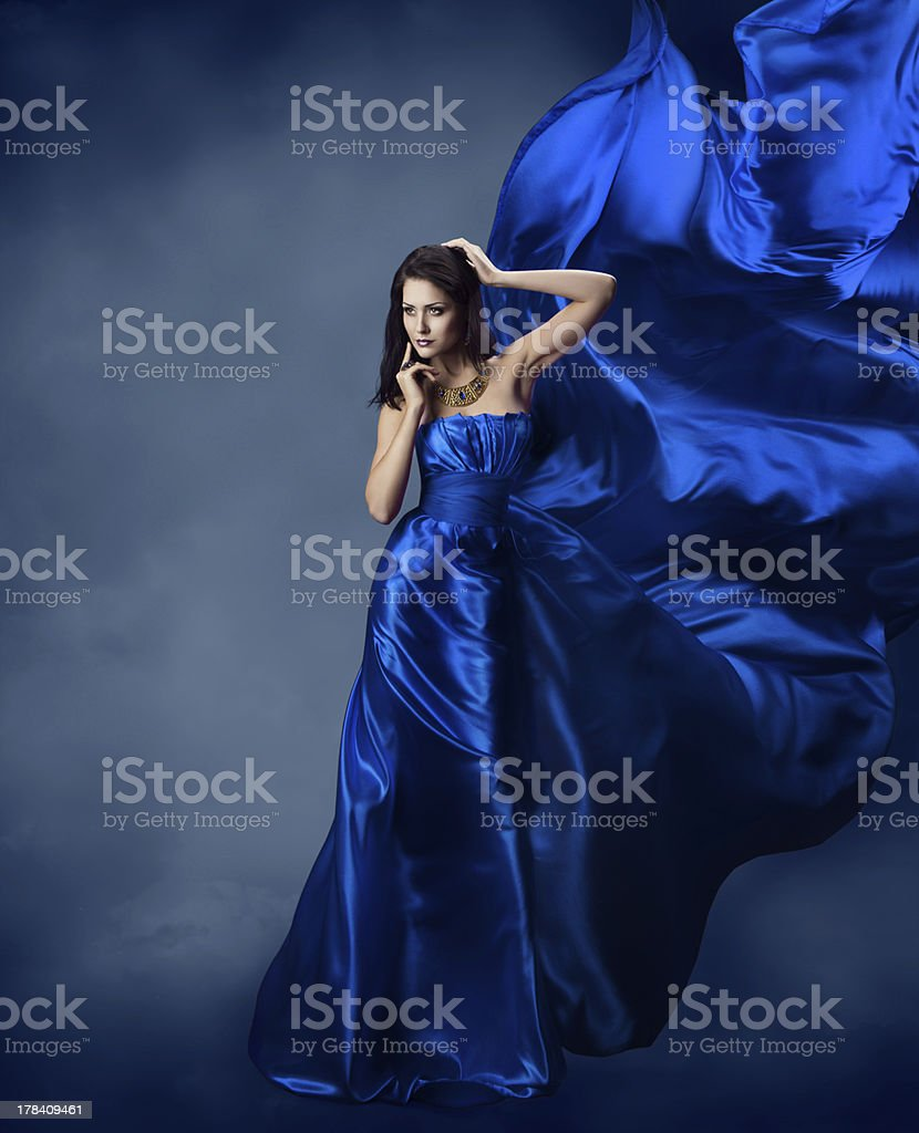 Woman in blue dress with flying silk fabric stock photo