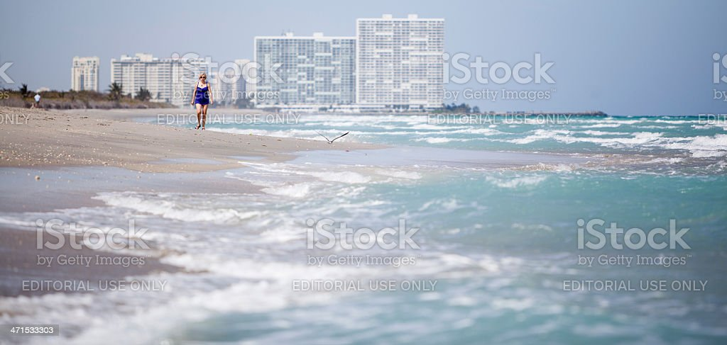 Woman in blue swimsuit walks on the beach royalty-free stock photo