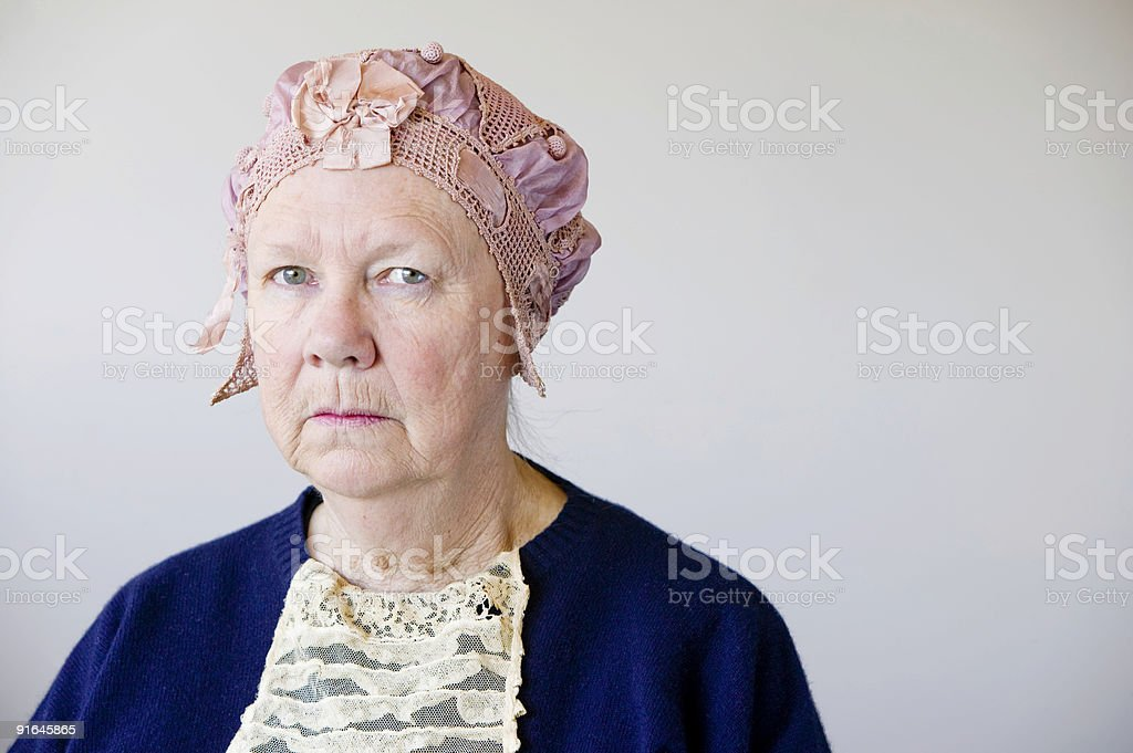 Woman in blue wearing a pink vintage hat royalty-free stock photo