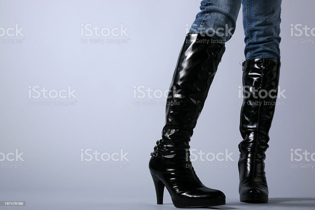 woman in boots on grey stock photo