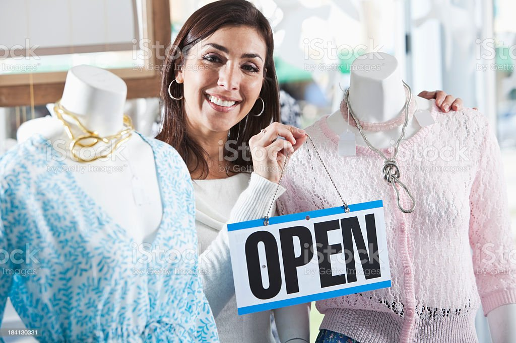 Woman in boutique with a open sign stock photo