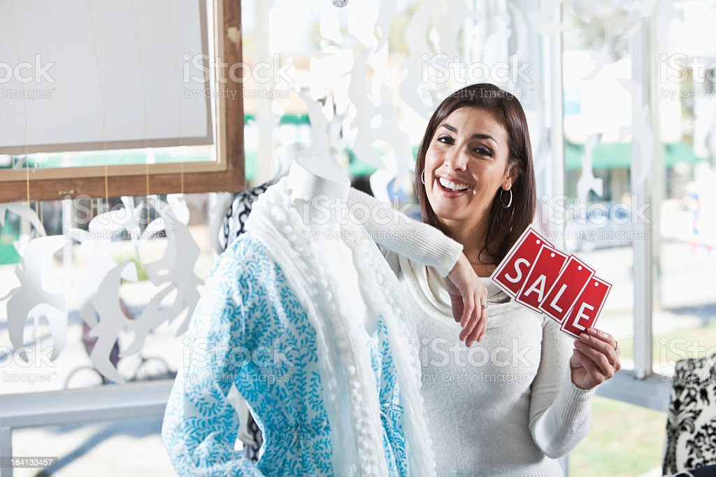 Woman in boutique with a sale sign stock photo