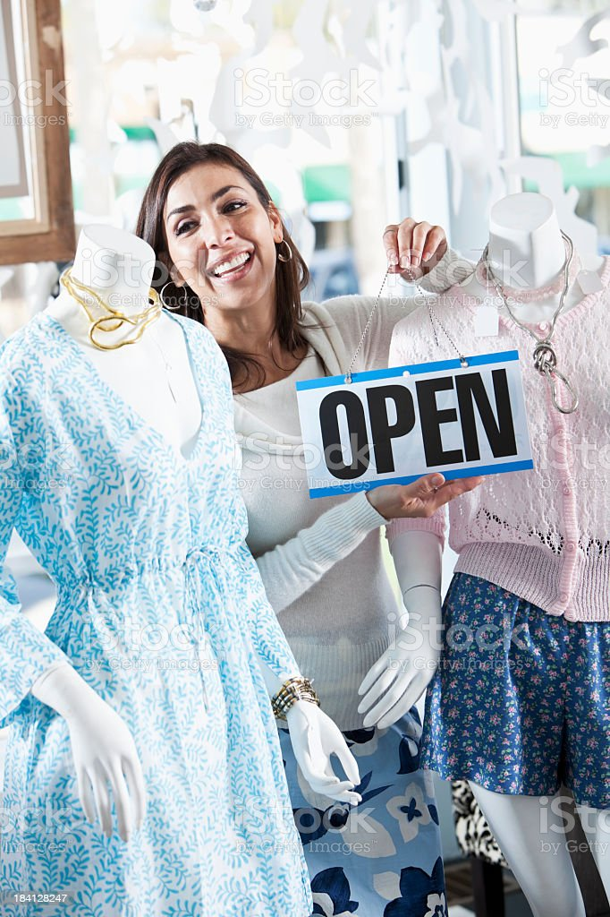 Woman in boutique with an open sign stock photo