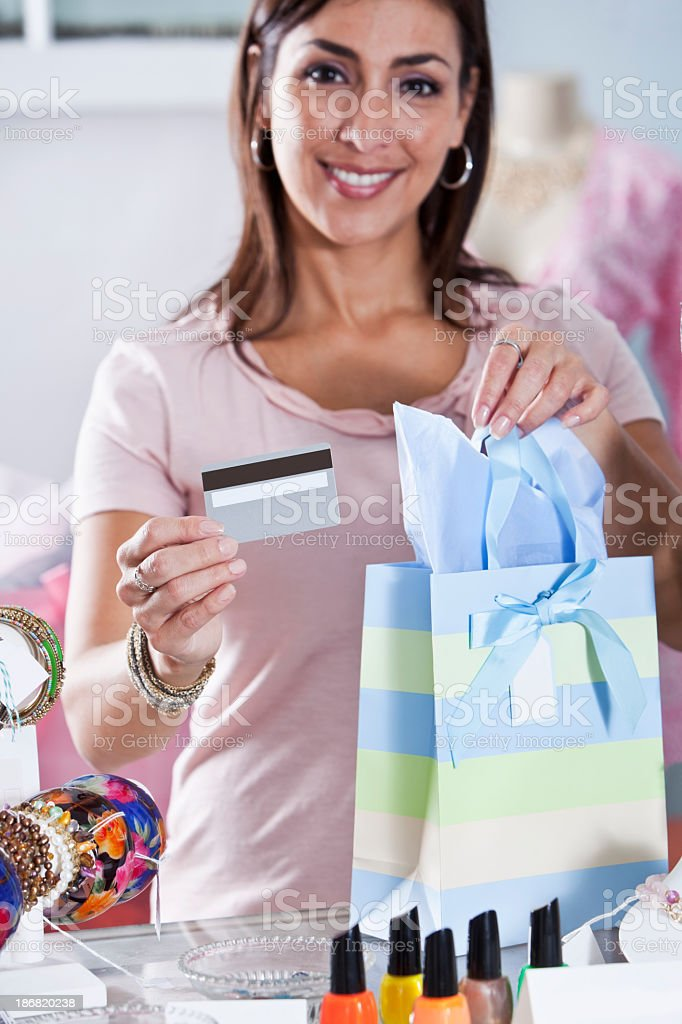 Woman in boutique with creditcard and shopping bag stock photo