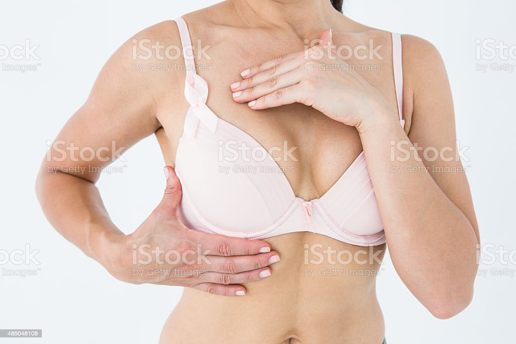 Woman in bra with breast cancer awareness ribbon stock photo