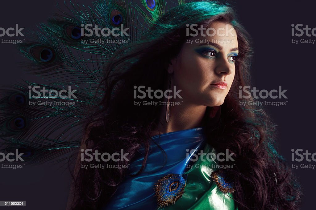 Woman in brilliant blue dress with peacock feathers design. Creative stock photo