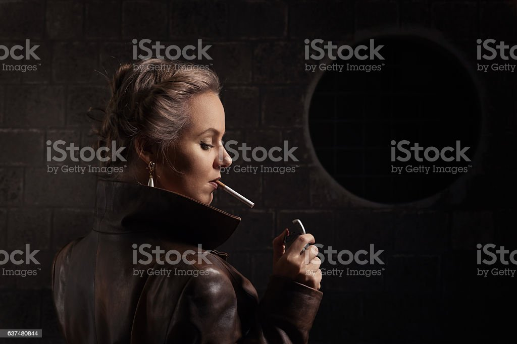 woman in brown leather coat with lighter and cigarette stock photo