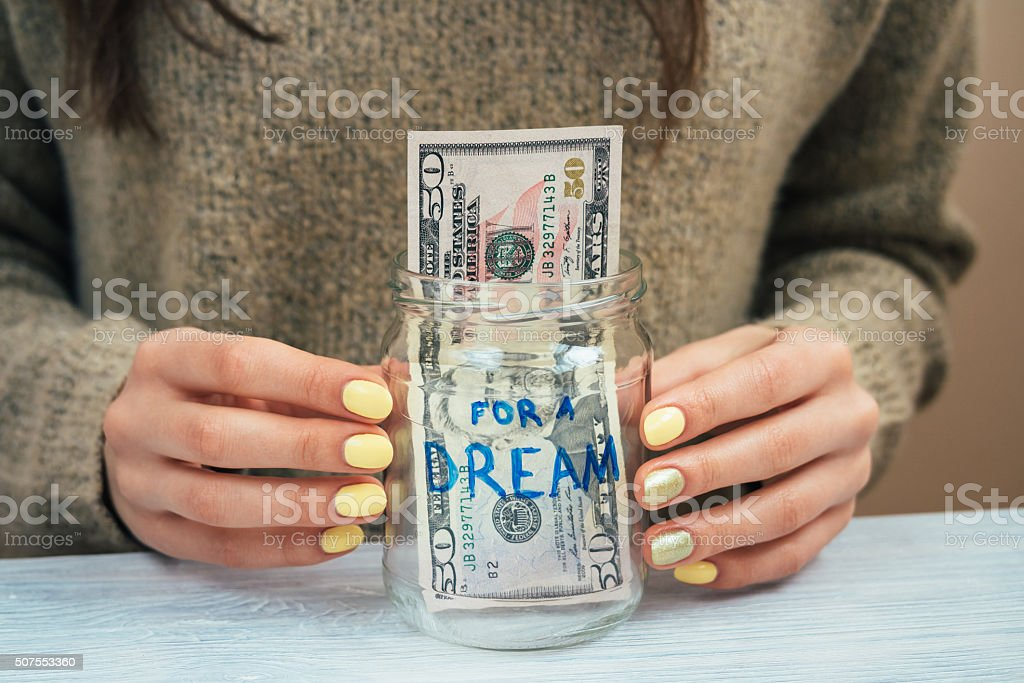 Woman in brown sweater puts money in a glass jar stock photo