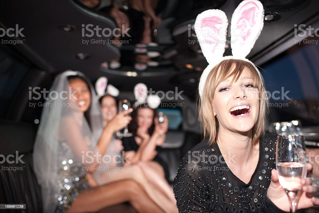 Woman in bunny ears drinking champagne in limo royalty-free stock photo