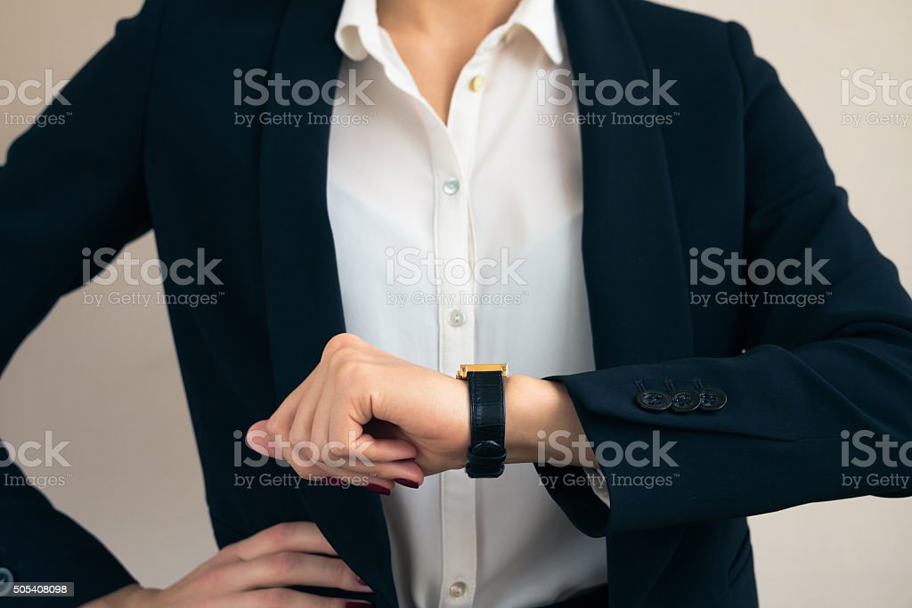 Woman in business suit looks on the watch stock photo