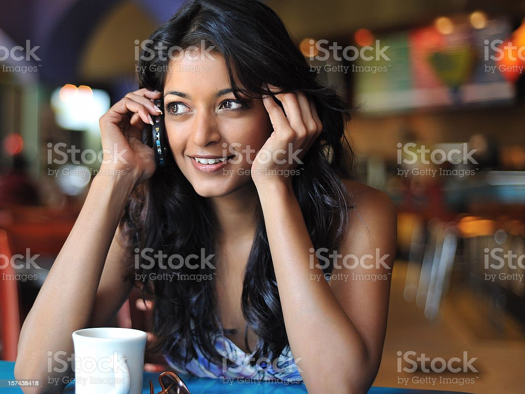 Woman in cafe sitting at table talking on phone and smiling  royalty-free stock photo