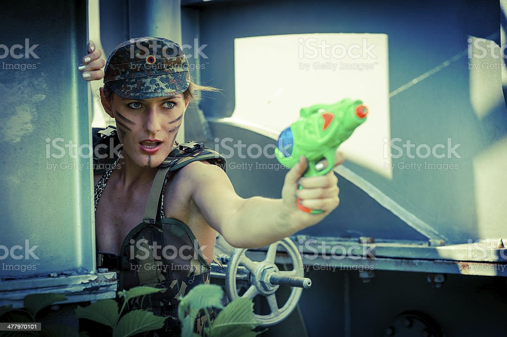 Woman in camouflage shoots from a water pistol royalty-free stock photo