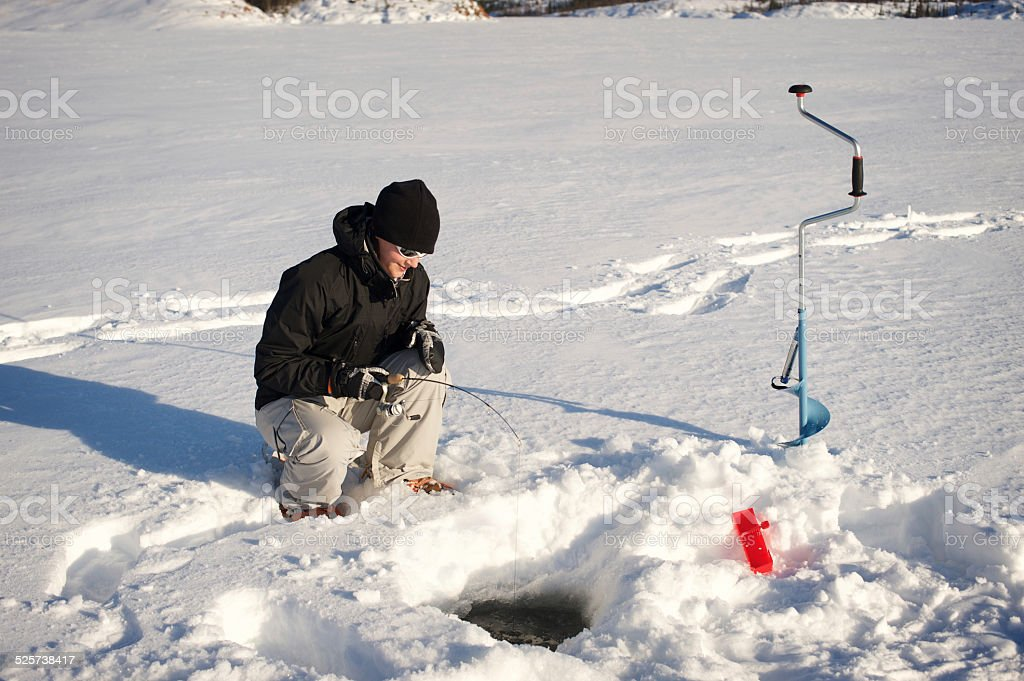 Woman in Canada's Arctic Ice Fishing. stock photo