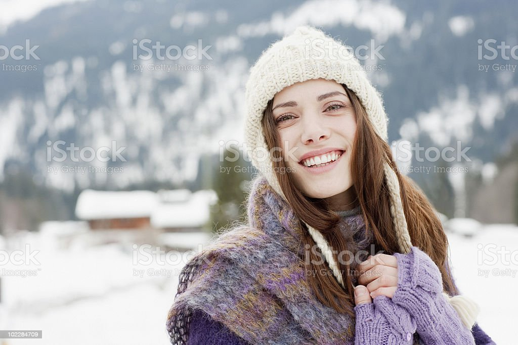 Woman in cap, scarf and gloves in snow stock photo