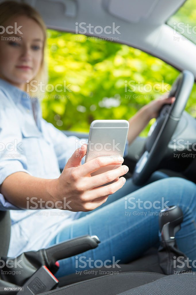 Woman In Car Texting On Mobile Phone Whilst Driving stock photo