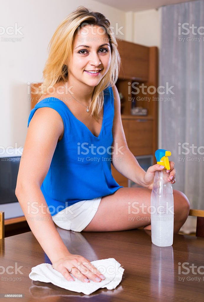 woman in casual cleaning at home and smiling stock photo