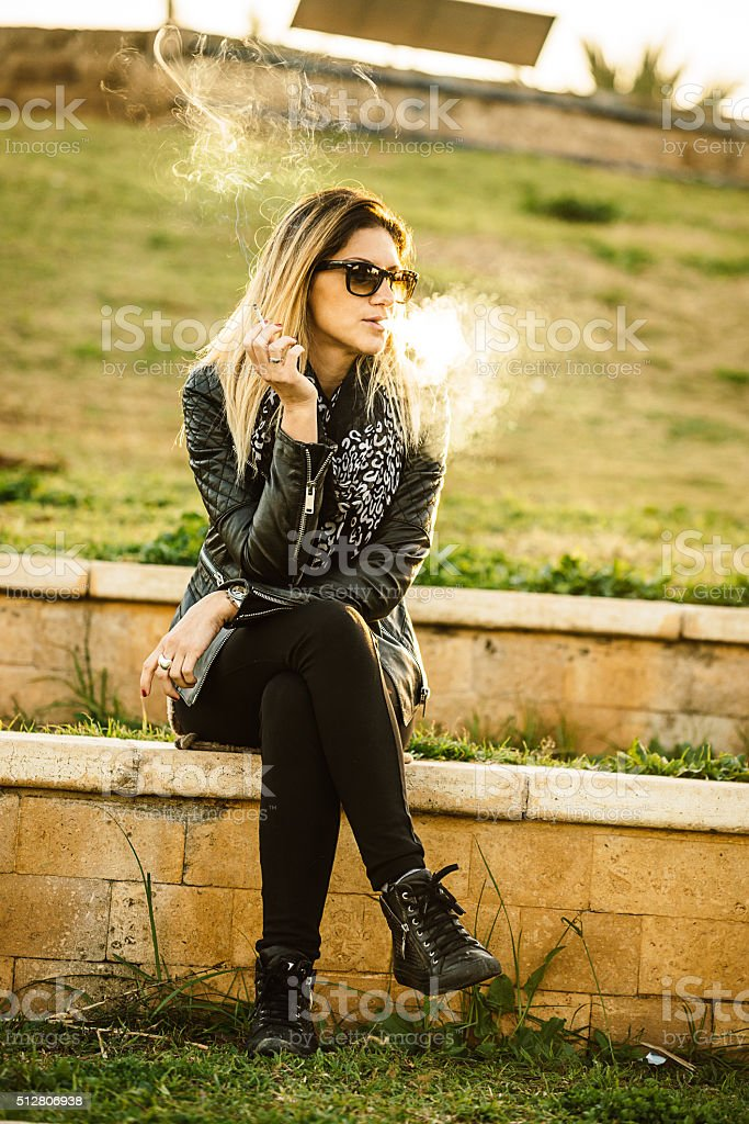 Woman in casual clothing sitting and smoking cigarette in park stock photo