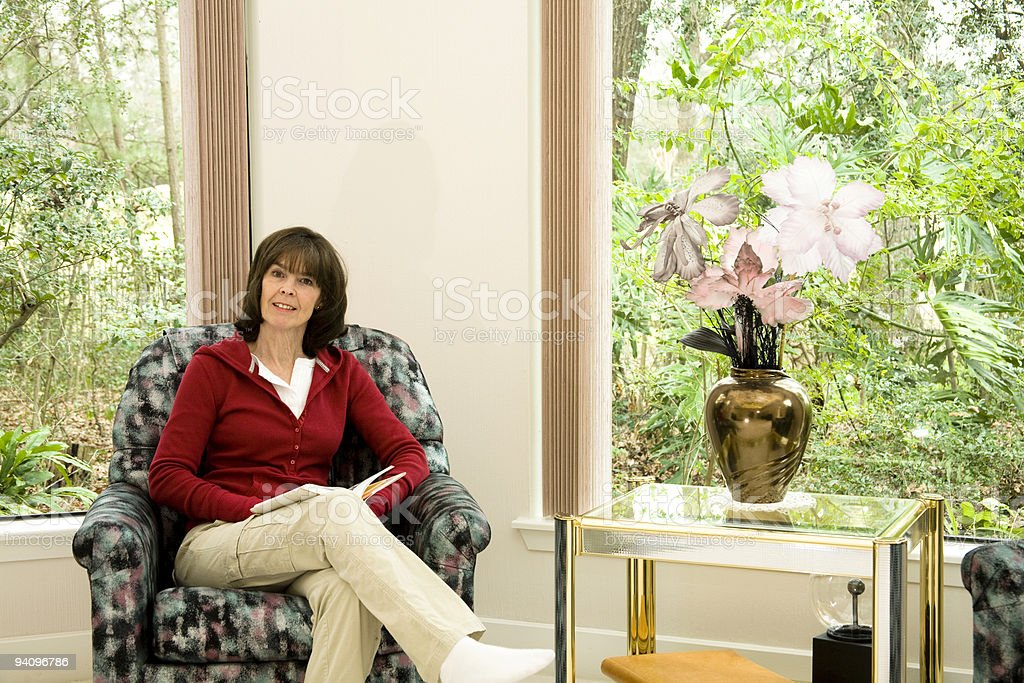 Woman in chair with book royalty-free stock photo